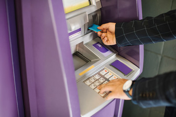 Hands of unrecognisable businessman putting credit card in atm.