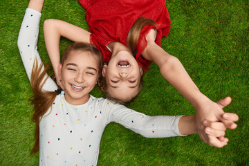 Cheerful girls lying on lawn