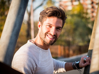 One handsome young man in urban setting in European city, standing and smiling to camera happy Fototapete