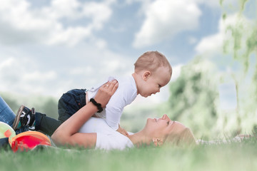 mom and her little son play together, lying on the lawn .