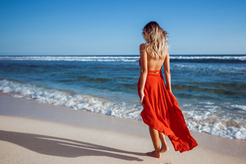 Girl walking on the beach in red dress back view