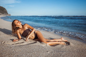 sexy girl in brown swimsuit sunbathing on the beach
