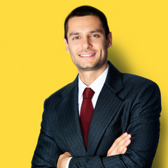 Happy businessman with crossed arms, on yellow