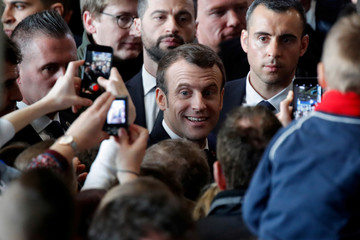 Visitors use mobile phones to photograph French President Emmanuel Macron as he visits at the International Agriculture Fair (Salon de l'Agriculture) in Paris