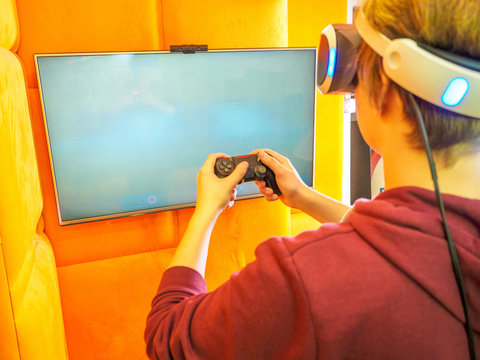 Teenager playing video game. blank white screen. place for your layout on the TV. Hands holding console controller. VR headset.