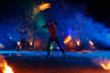 Fire show, dancing with flame, male master juggling with fireworks, performance outdoors, draws a fiery figure in the dark, bright sparks in the night.