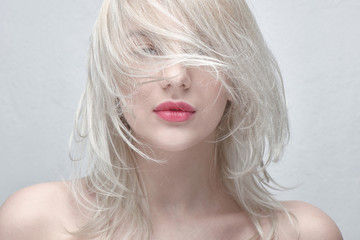 Portrait of a young beautiful blonde woman with plump red lips and bare shoulders on a white background close up. Fashionable fancy hairstyle