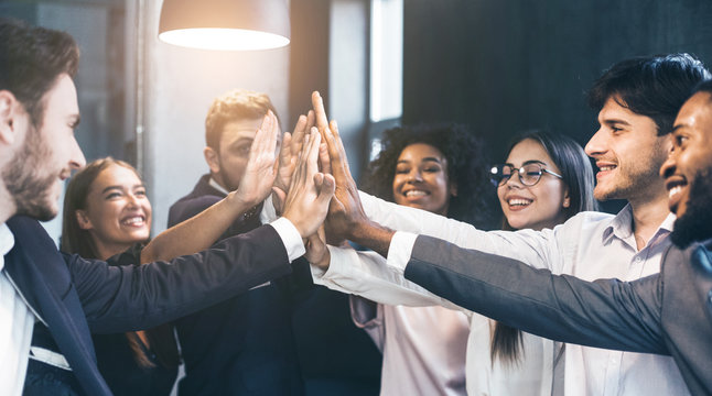 Happy office workers giving high five at meeting