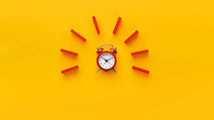 Alarm clock with red dominoes on yellow background Wall mural