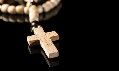 Wooden rosary beads with cross on black reflective background. Space for text.