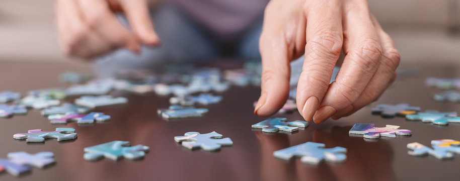 Elderly woman hands doing jigsaw puzzle closeup