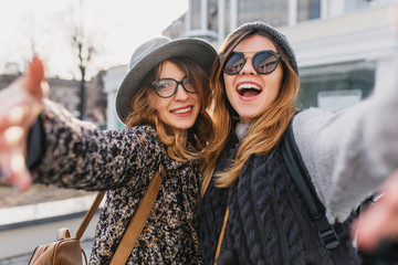 Excited girls in stylish glasses having fun durning morning walk around city. Outdoor portrait of two joyful friends in trendy hats making selfie and laughing, waving hands.