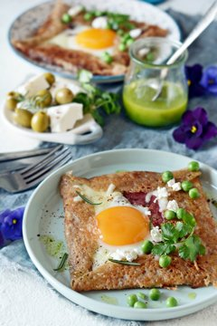 Breton traditional pancake made from buckwheat flour with ham, cheese, egg, feta, green peas and green butter. Breakfast of buckwheat thin pancakes with fried eggs, ham and cheese.