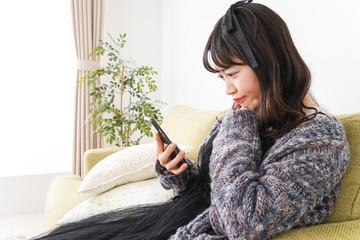 家でスマートフォンを使う若い女性
