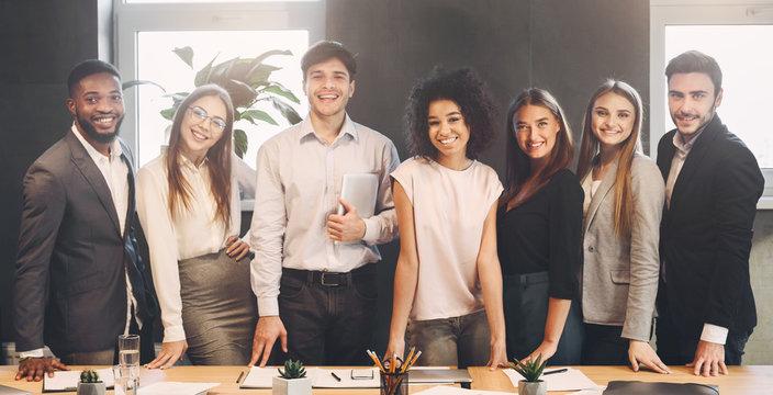 Successful business team looking at camera in office