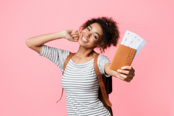 Happy woman showing passport and tickets over background