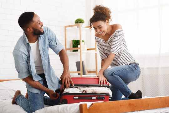 African-american couple trying to close suitcase on bed