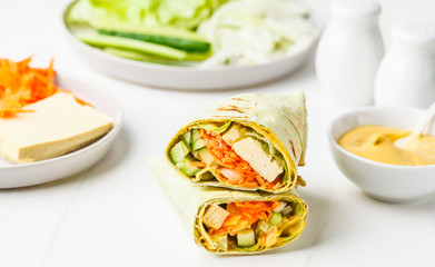 Cooking vegan tofu wraps with cashew cheese sauce and vegetables, white background.