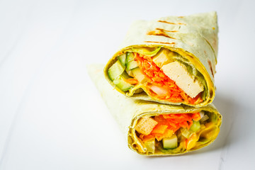 Vegan tofu wraps with cashew cheese sauce and vegetables, white background.