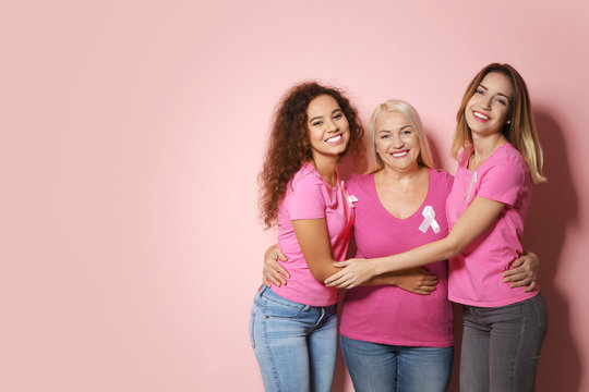 Group of women with silk ribbons and space for text on color background. Breast cancer awareness concept