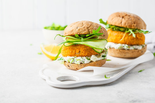 Fish burger with cucumber, arugula and mayonnaise sauce, white background, copy space.