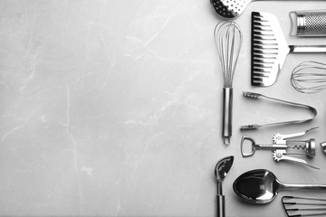Different kitchen utensils on grey background, top view with space for text