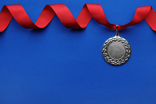 Gold medal with space for design on color background, top view. Victory concept