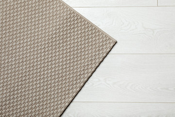 Woven mat on wooden background, top view with space for text