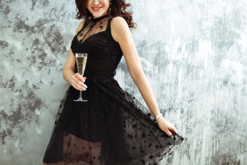 Smiling woman in black dress with a glass of champagne.