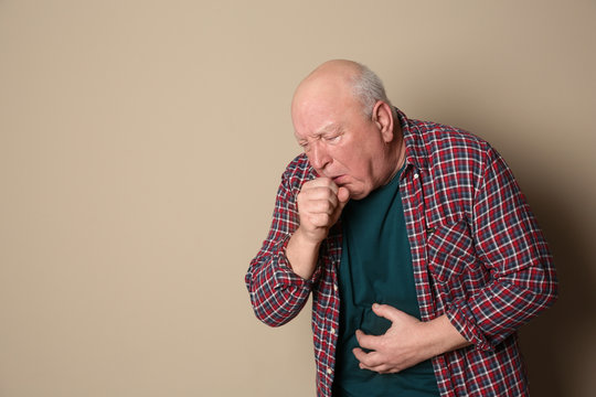Senior man suffering from cough on color background. Space for text