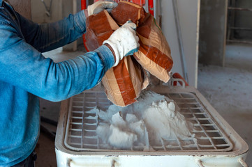 worker pours the contents of a bag of premixed mortar into a cochlea mixer