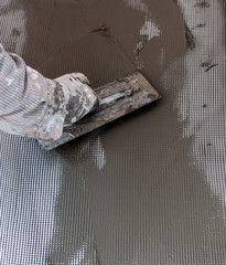 Worker makes plaster on a wall with mesh and glue