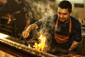Tasty beef steak cooked on grill with fire and smoke. Beautiful brutal man with bearded face and tattoo cooking meat. Professional chef wearing apron in restaurant kitchen. Wall mural