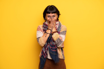 Young hippie woman over yellow wall smiling a lot