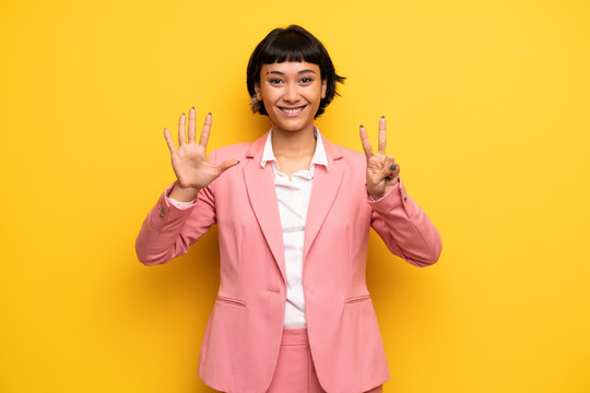 Modern woman with pink business suit counting seven with fingers