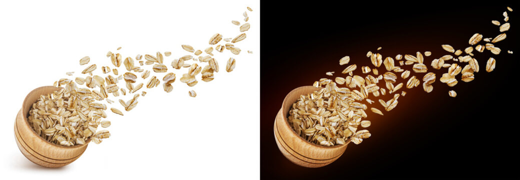 Oat flakes flying out of wooden bowl isolated on white and black background