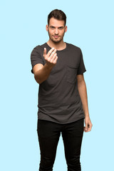 Man with black shirt inviting to come with hand. Happy that you came over blue background