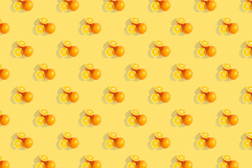Oranges on bright colored yellow background. Repeating pattern, preparation for wallpaper citrus mood.