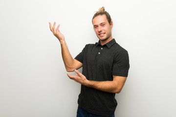 Blond man with long hair over white wall extending hands to the side for inviting to come