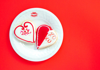 two heart shaped decorated cookies and a lipstick kiss on a white plate with a red background with copy space