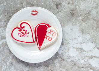 two heart shaped decorated cookies and a red lipstick kiss on a white plate atop a gray marble counter with copy space