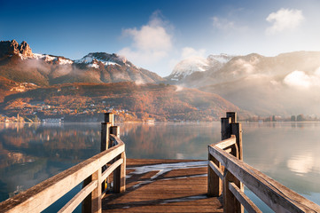 Wooden pier on Annecy lake in winter. Alps mountains, France.