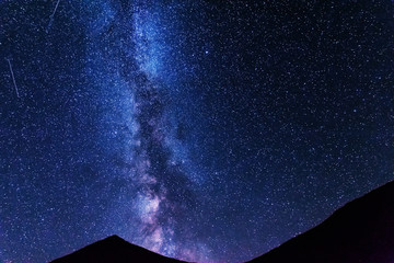 A bright starry night with millions of stars and a galaxy Milky way from the altitude of the mountain ranges.