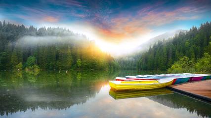 Boats on majestic mountain lake Lacul Rosu or Red Lake or Killer Lake Fototapete