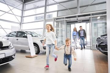 Family entering car dealership, happy children running.
