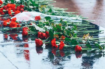 Flowers lie on granite near the monument