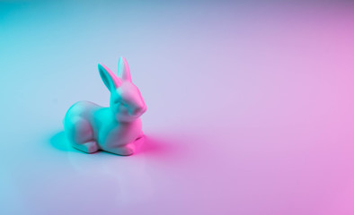 White Easter bunny with colorful ultraviolet holographic neon lights. Creative concept.