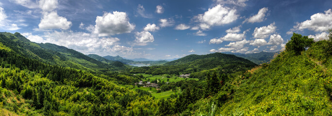 Panorama of a small village at the bottom of a bright green valley in rural China