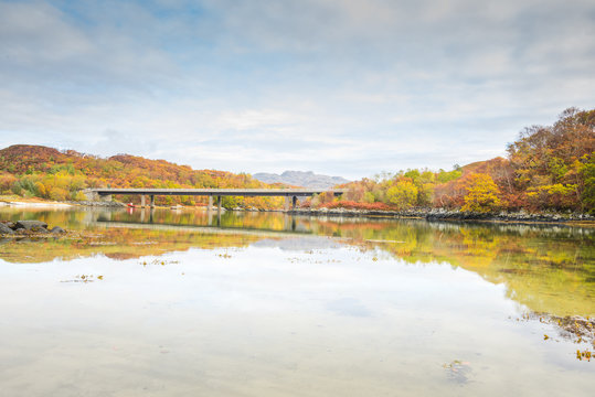 The bridge carrying the A830 road over the River Morar, near Morar, Highlands of Scotland - autumn scenery with orange leaves and trees reflected in water