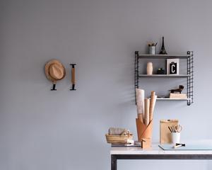 Details eines Zimmers: Arbeitsplatz, Schreibtisch, Wandregal, Wandhaken, Papierrollen